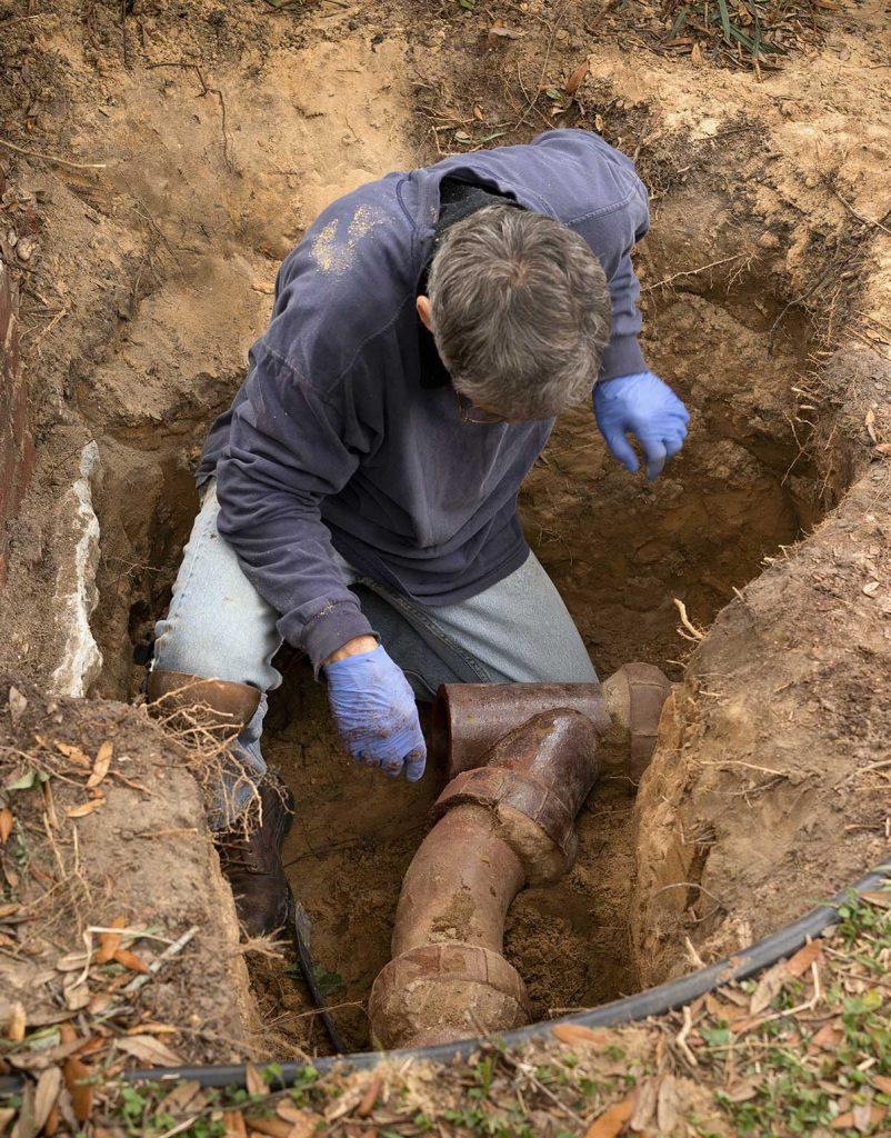 man fixing underground pipe