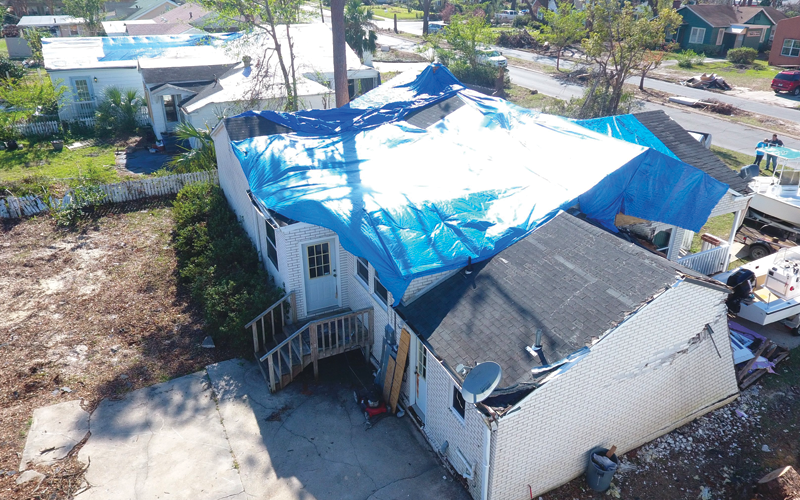 Damaged house with blue tarp